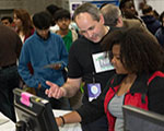 NIGMS Director Dr. Jon R. Lorsch explains a protein letter computer activity to a young participant at the USA Science and Engineering Festival